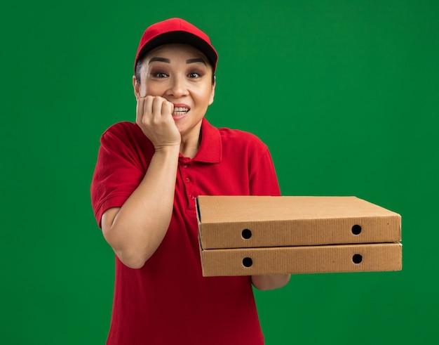 Giovane donna delle consegne in uniforme rossa e cappello che tiene in mano scatole per pizza stressata e nervosa