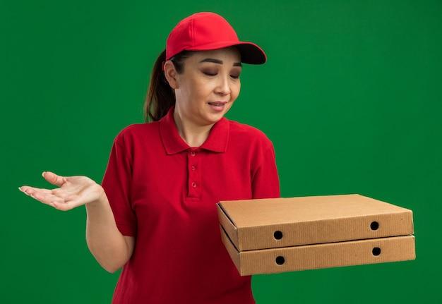 Giovane donna delle consegne in uniforme rossa e berretto che tiene in mano scatole di pizza che sembrano confuse con il braccio in fuori in piedi sul muro verde