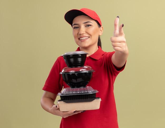 Giovane donna di consegna in uniforme rossa e cappuccio che tiene pila di confezioni di cibo che punta con il dito indice davanti sorridendo allegramente in piedi sopra la parete verde