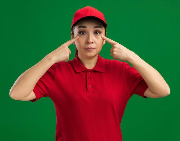 Giovane donna delle consegne in uniforme rossa e berretto che punta con il dito indice agli occhi che sembra fiduciosa in piedi sul muro verde