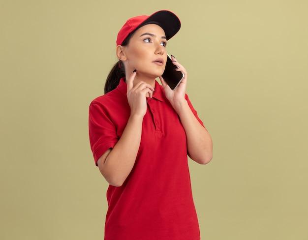 Giovane donna delle consegne in uniforme rossa e cappuccio parlando al telefono cellulare con la faccia seria in piedi sopra la parete verde