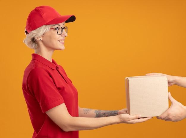 Giovane donna di consegna in uniforme rossa e cappello con gli occhiali che danno la scatola di cartone al cliente che sorride amichevole che sta sopra la parete arancione