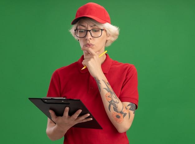 Giovane donna di consegna in uniforme rossa e berretto con gli occhiali che tengono appunti e matita guardando con faccia seria pensando in piedi sopra la parete verde