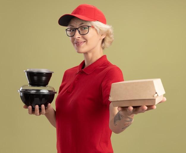 Giovane donna delle consegne in uniforme rossa e cappello con gli occhiali che tengono i pacchetti di cibo smilign fiducioso in piedi sopra la parete verde