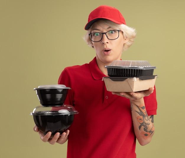 Giovane donna di consegna in uniforme rossa e cappello con gli occhiali che tengono i pacchetti di cibo sorridente confuso in piedi sopra la parete verde