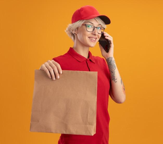 Giovane donna di consegna in uniforme rossa e berretto con gli occhiali in possesso di pacchetto di carta parlando al telefono cellulare sorridente fiducioso in piedi sopra la parete arancione