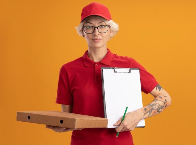 Giovane donna di consegna in uniforme rossa e berretto con gli occhiali che tengono la scatola della pizza e gli appunti con la matita che sembra in piedi sicura sopra la parete arancione