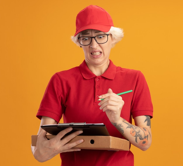 Young delivery woman in red uniform and cap wearing glasses holding pizza box and clipboard with pencil looking confused and disappointed standing over orange wall
