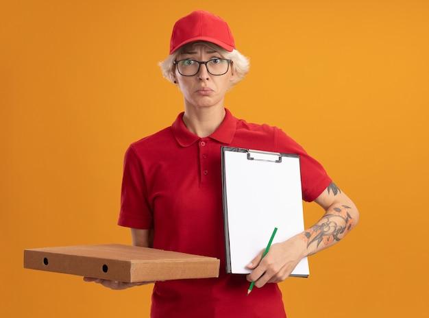 Giovane donna delle consegne in uniforme rossa e cappello con gli occhiali tenendo la scatola della pizza e appunti con la matita che sembra confuso e molto ansioso in piedi sopra la parete arancione