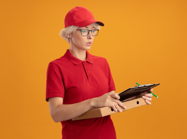Young delivery woman in red uniform and cap wearing glasses holding pizza box and clipboard with pencil looking confused and very anxious standing over orange wall