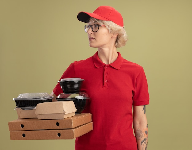 Young delivery woman in red uniform and cap wearing glasses holding pizza boxes and food packages looking aside with serious face standing over green wall