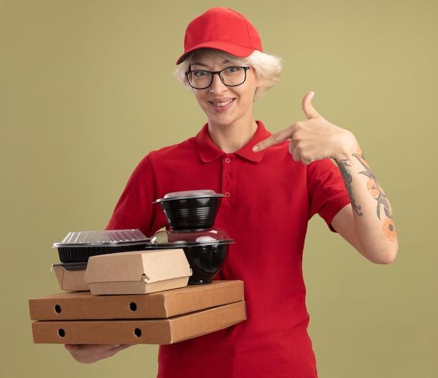 Giovane donna delle consegne in uniforme rossa e cappello con gli occhiali che tengono le scatole della pizza e i pacchetti di cibo che punta con il dito indice a loro sorridendo allegramente in piedi sopra la parete verde