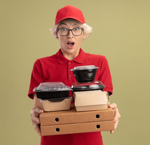Giovane donna delle consegne in uniforme rossa e berretto con gli occhiali in possesso di scatole per pizza e confezioni di cibo sorpreso e stupito in piedi sopra la parete verde