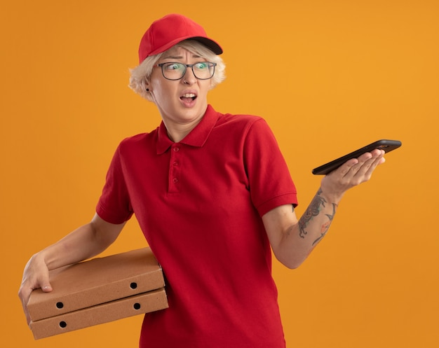 Young delivery woman in red uniform and cap wearing glasses holding pizza boxes looking at her smartphone being confused standing over orange wall