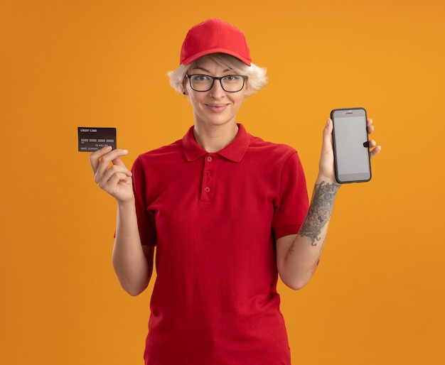 Young delivery woman in red uniform and cap wearing glasses showing smartphone and credit card smiling confident standing over orange wall
