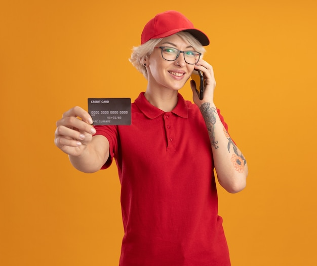 Young delivery woman in red uniform and cap wearing glasses talking on mobile phone showing credit card smiling confident  standing over orange wall