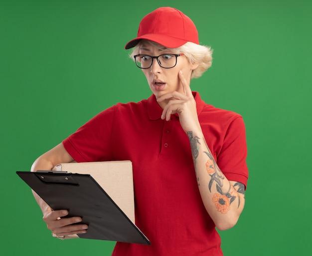 Giovane donna delle consegne in uniforme rossa e cappello con gli occhiali con la scatola di cartone guardando gli appunti in mano con espressione confusa in piedi sopra la parete verde