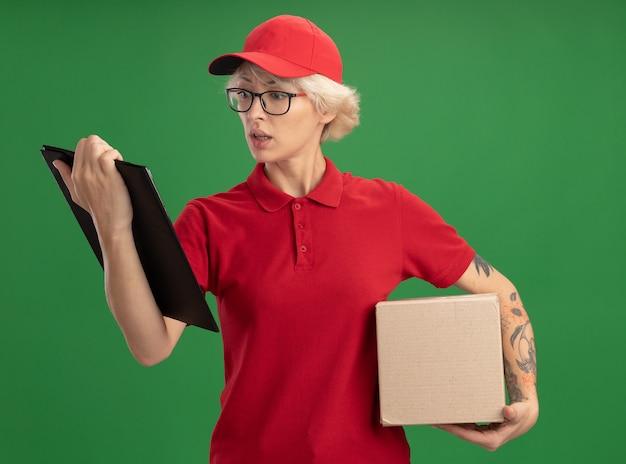 Giovane donna di consegna in uniforme rossa e berretto con gli occhiali con scatola di cartone guardando appunti preoccupato in piedi sopra la parete verde