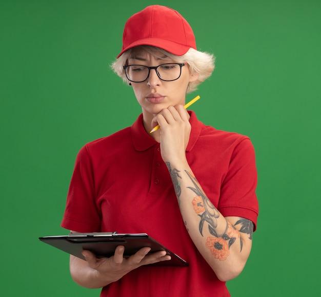 Giovane donna delle consegne in uniforme rossa e cappello con gli occhiali con appunti con pagine vuote e matita guardando verso il basso con faccia seria pensando in piedi sopra la parete verde