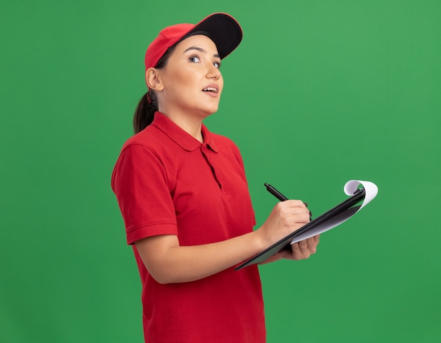 Giovane donna di consegna in uniforme rossa e cappuccio con appunti e matita che osserva in su con espressione pensierosa pensando in piedi sopra la parete verde