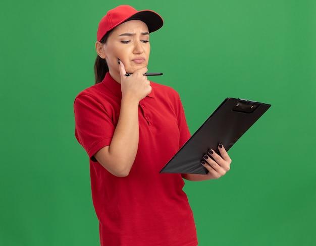 Giovane donna di consegna in uniforme rossa e cappuccio con appunti e matita che guarda con espressione pensierosa sul pensiero del viso in piedi sopra la parete verde