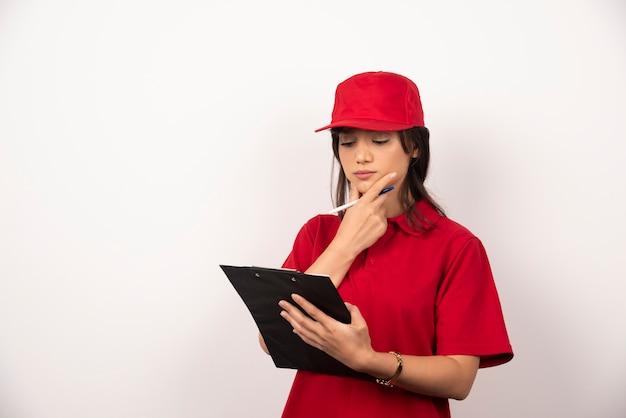 Giovane donna di consegna in uniforme rossa con appunti su sfondo bianco.