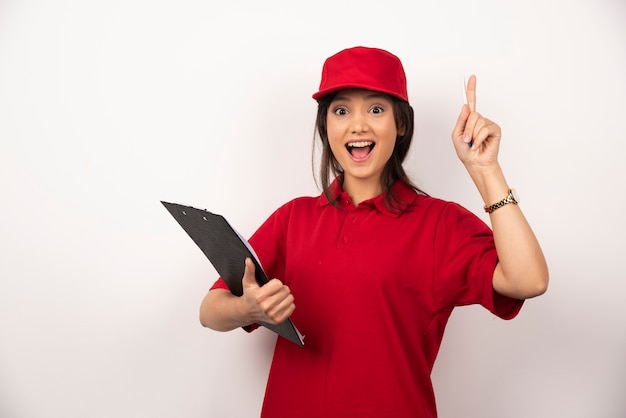 Young delivery woman in red uniform with clipboard on white background.