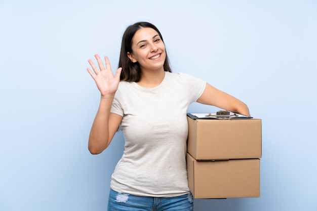 Young delivery woman saluting with hand with happy expression