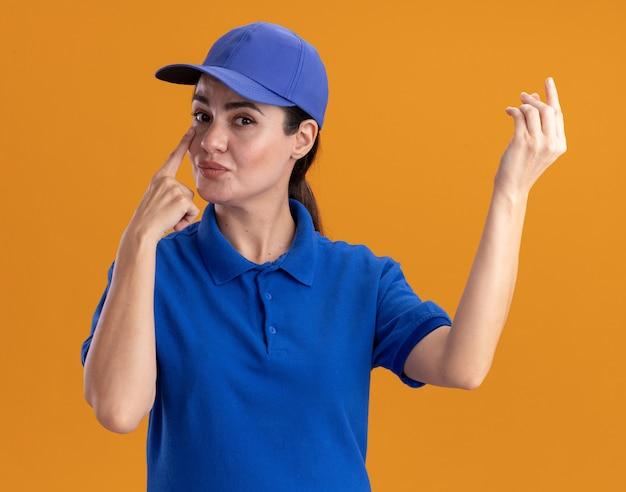 Giovane donna delle consegne in uniforme e berretto che fa un gesto di denaro mettendo il dito sotto l'occhio