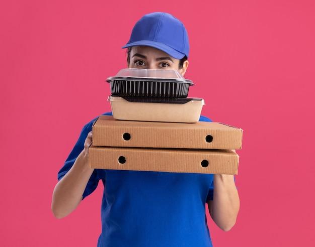 Giovane donna delle consegne in uniforme e berretto che tiene i pacchetti di pizza con pacchetto di cibo di carta e contenitore per alimenti su di loro guardando davanti da dietro di loro isolato sul muro rosa