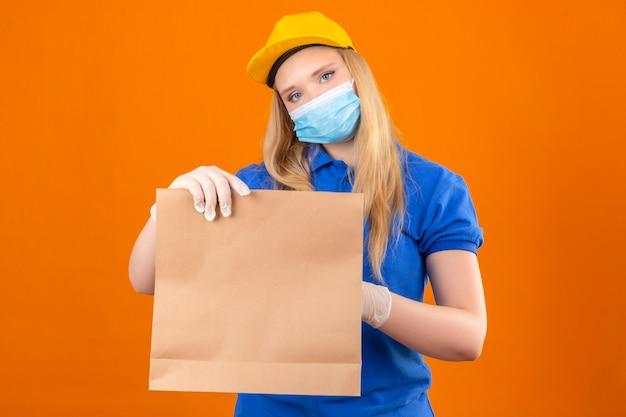 分離された暗い黄色の背景に自信を持って探している手で医療用マスクを示す紙のパッケージで青いポロシャツと黄色のキャップを着ている若い配達の女性