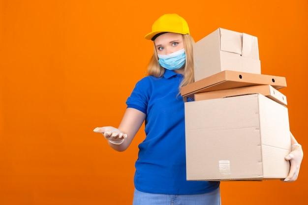 파란색 폴로 셔츠와 격리 된 어두운 노란색 배경 위에 지불을 기다리는 열린 손으로 상자의 스택과 함께 노란색 모자 서 입고 젊은 배달 여자 무료 사진