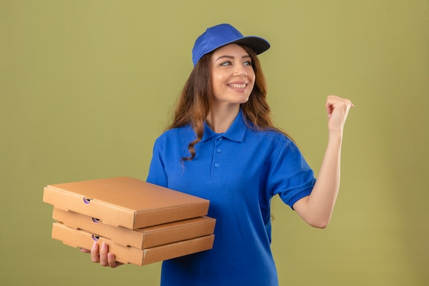 Young delivery woman wearing blue polo shirt and cap standing with pizza boxes looking aside smiling pointing with finger to the side over isolated green background