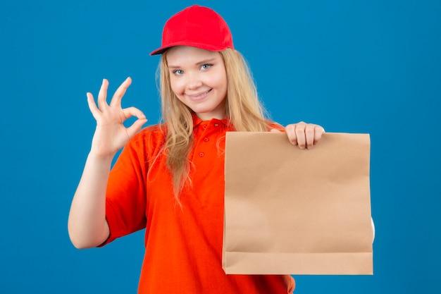 オレンジ色のポロシャツと紙のパッケージを保持している赤い帽子を身に着けている若い配達の女性が孤立した青い背景にフレンドリーなokサインをしている紙のパッケージを保持