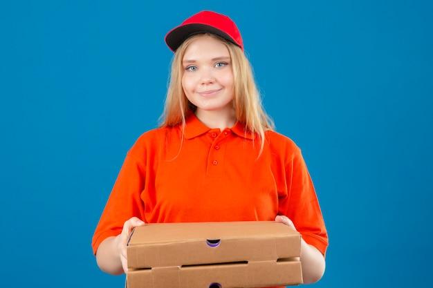 オレンジ色のポロシャツと分離の青い背景の上の顔に笑顔でカメラを見てピザの箱を保持している赤い帽子を着ている若い配達の女性
