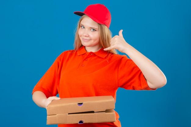 オレンジ色のポロシャツとピザの箱を保持している赤い帽子を身に着けている若い配達の女性が分離の青い背景にフレンドリーな笑みを浮かべてジェスチャーをかける