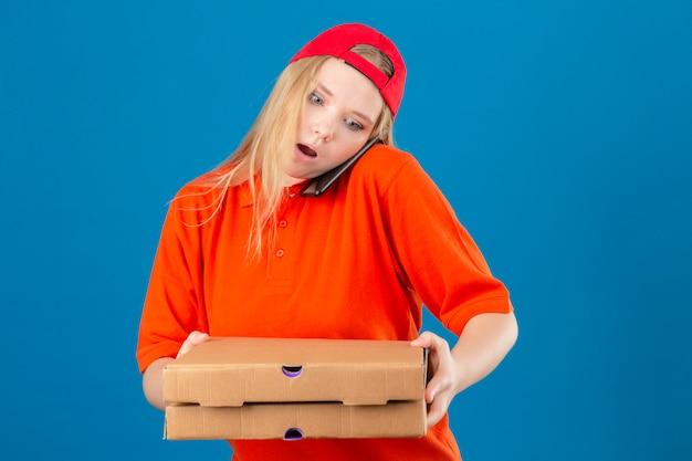 オレンジ色のポロシャツと携帯電話で話しながらピザの箱を持って赤い帽子を身に着けている若い配達の女性が分離の青い背景に驚きの顔でショックで怖い