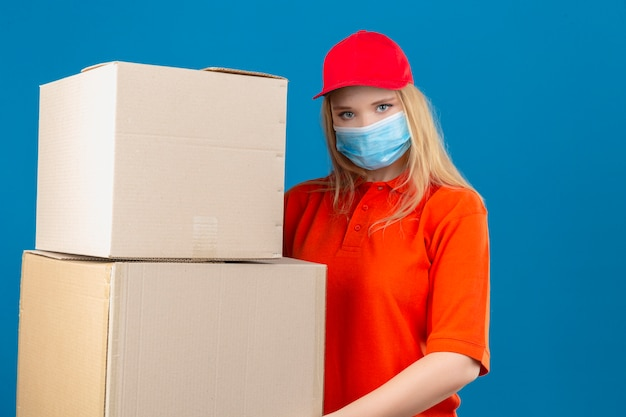 孤立した青い背景に深刻な顔でカメラを見て大きな段ボール箱を保持している医療用防護マスクでオレンジ色のポロシャツと赤い帽子を着ている若い配達の女性
