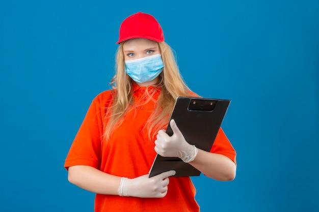孤立した青い背景に深刻な顔でカメラを見て手にクリップボードで立っている医療用防護マスクにオレンジ色のポロシャツと赤い帽子を着ている若い配達の女性