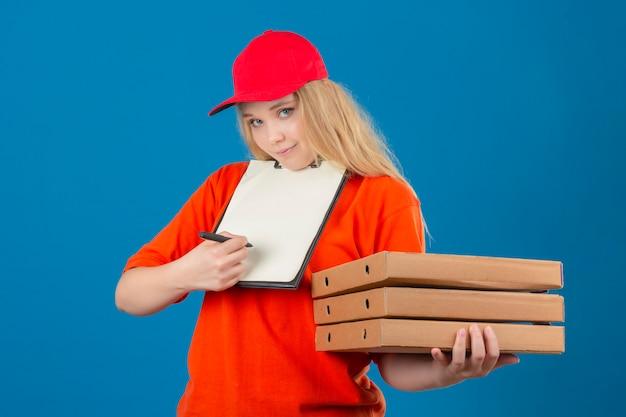 Молодая женщина-доставщик в оранжевой рубашке поло и красной кепке в медицинской защитной маске стоит со стопкой коробок для пиццы и буфером обмена с ручкой, просящей подписи на изолированном синем фоне
