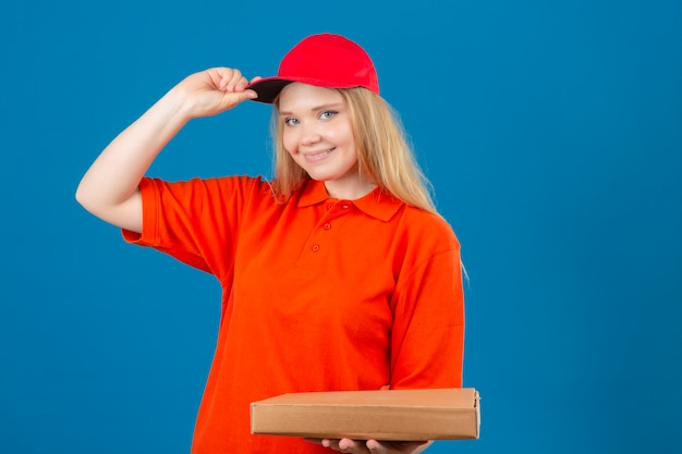Молодая курьерская женщина в оранжевой рубашке поло и красной кепке приветствует улыбку и дружелюбно трогает ее кепку, стоящую на изолированном синем фоне