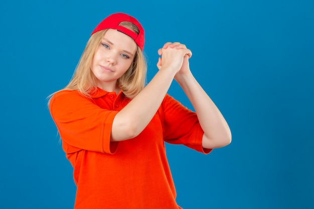 Young delivery woman wearing orange polo shirt and red cap gesturing with clasped looking confident and proud over isolated blue background