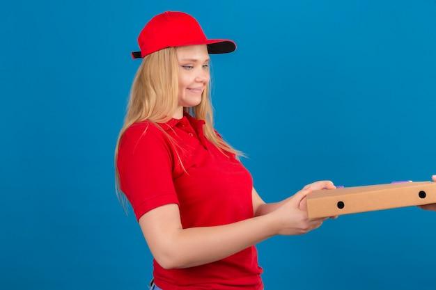 Молодая курьерская женщина в красной рубашке поло и кепке дает клиенту коробку из-под пиццы, дружелюбно улыбаясь на синем фоне