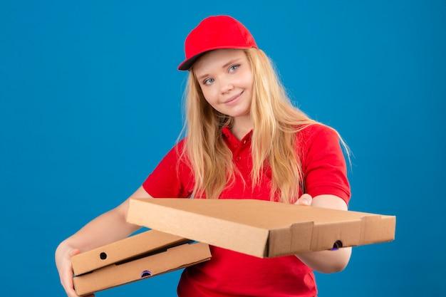 Молодая курьерская женщина в красной рубашке поло и кепке дает покупателю коробки с пиццей с улыбкой на лице на изолированном синем фоне