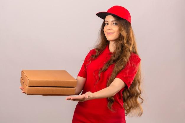 Молодая курьерская женщина в красной рубашке поло и кепке дает покупателю коробки с пиццей, дружелюбно улыбаясь на изолированном белом фоне
