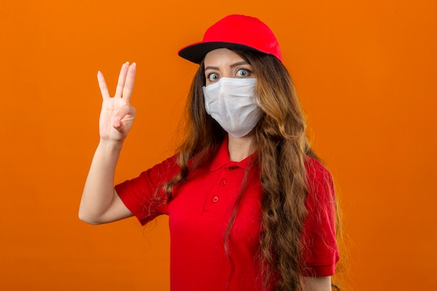 孤立したオレンジ色の背景上でokサインをして驚いて探している医療防護マスクで赤いポロシャツとキャップを着ている若い配達の女性