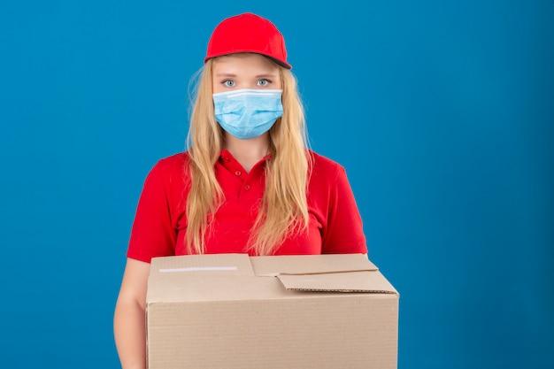 孤立した青い背景に深刻な顔でカメラを見て段ボール箱で立っている医療防護マスクで赤いポロシャツとキャップを着ている若い配達の女性