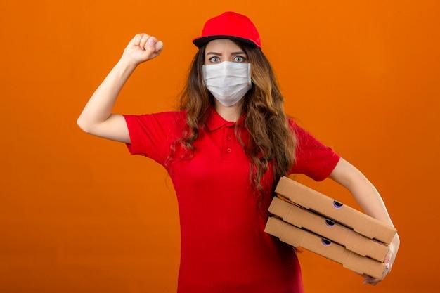孤立したオレンジ色の背景に深刻な顔の勝者の概念と握りこぶしを上げるピザの箱で立っている医療防護マスクに赤いポロシャツとキャップを着ている若い配達の女性