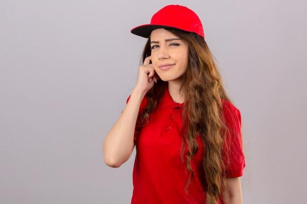 赤いポロシャツと分離の白い背景の上の疑いでカメラを見て目を細めてカメラを見てキャップを着ている若い配達の女性