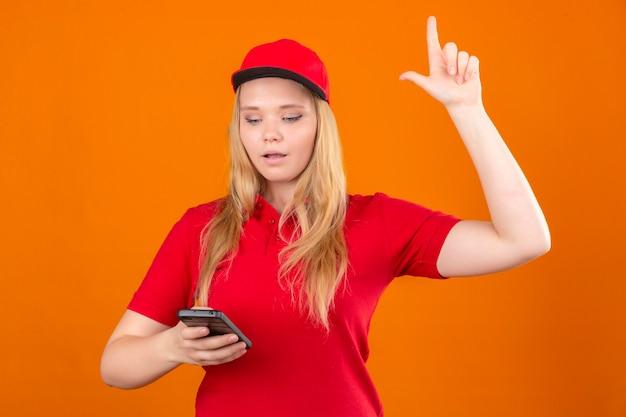 Молодая женщина-доставщик в красной рубашке поло и кепке смотрит на мобильный телефон в руке и показывает указательным пальцем вверх, имея новую концепцию идеи на изолированном оранжевом фоне